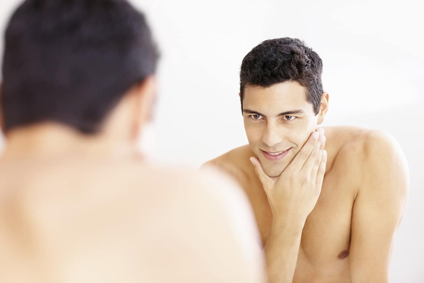 Reflection of a young man in the bathroom mirror after shaving