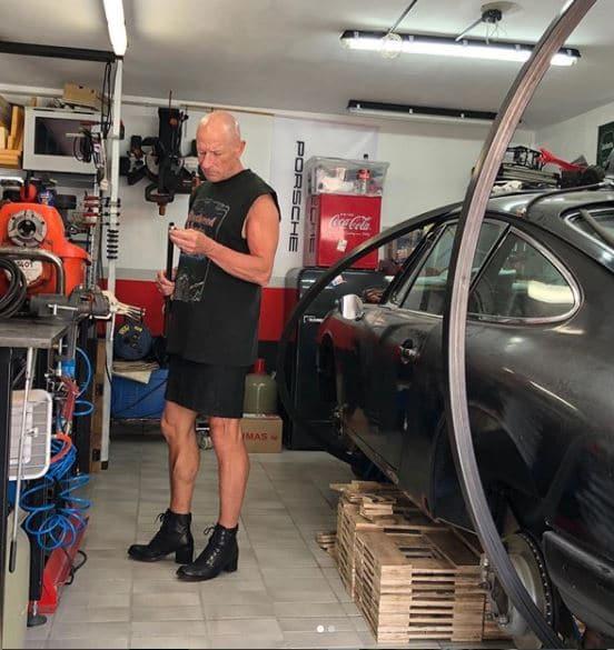 homem de saia na oficina de carro