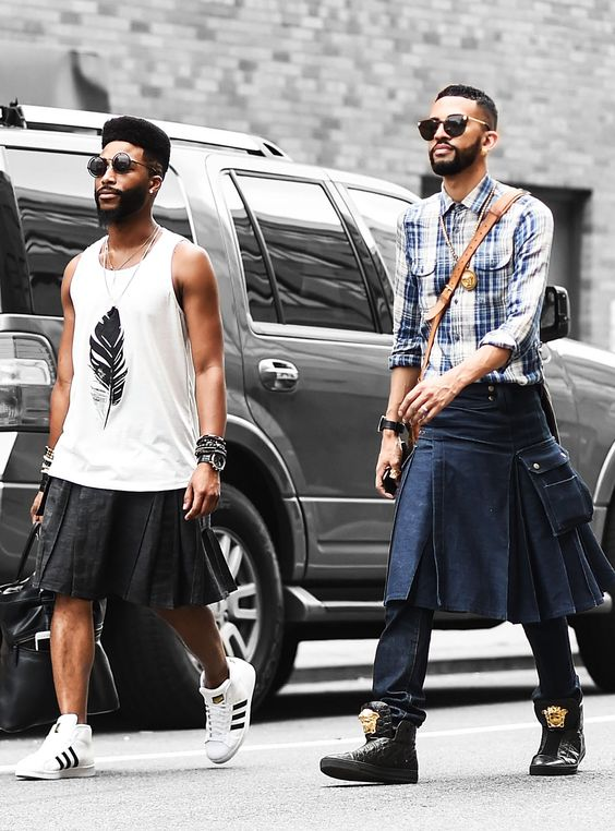 Dois homens negros caminhando na rua de saia