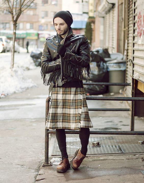 Homem com saia xadrez em pé na rua