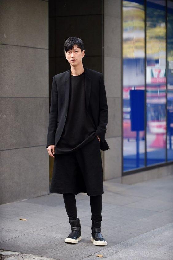 Homem asiático de saia preta e blazer