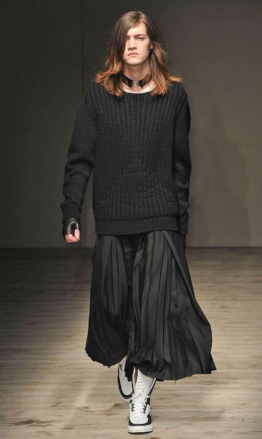 Modelo masculino na passarela com saia longa preta