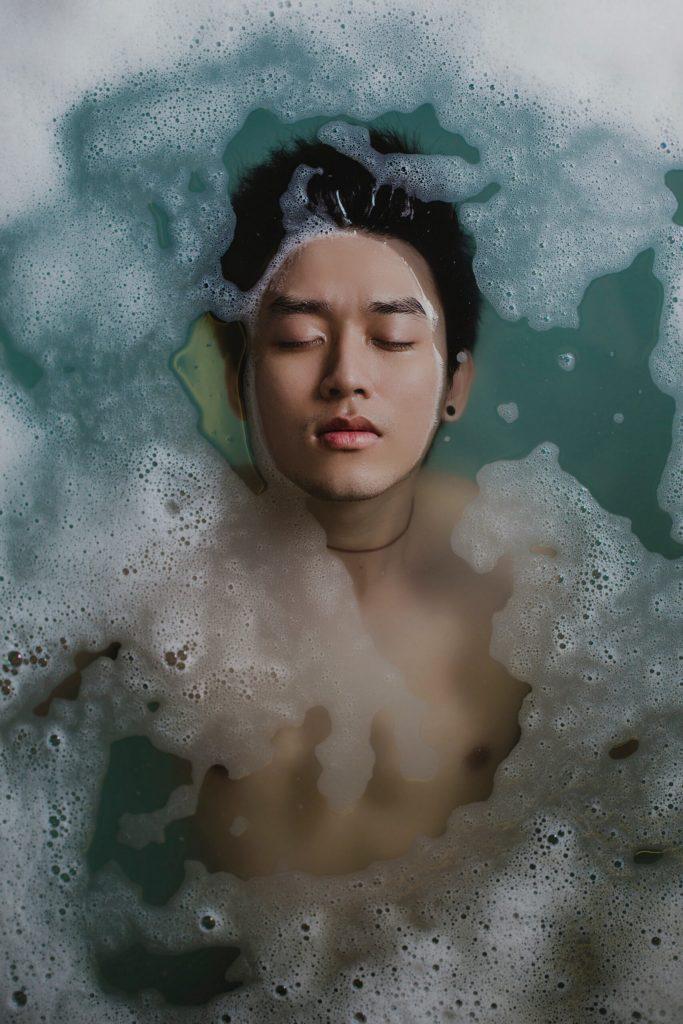 Homem jovem deitado em uma banheira com a face exposta