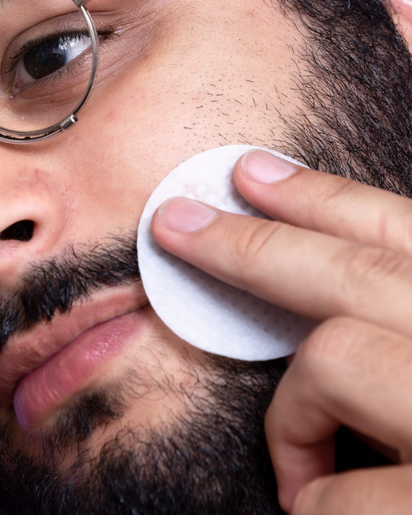 Homem com barba limpando o rosto com algodão