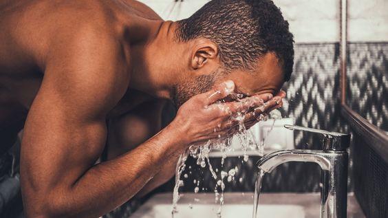 Homem negro lavando o rosto na torneira