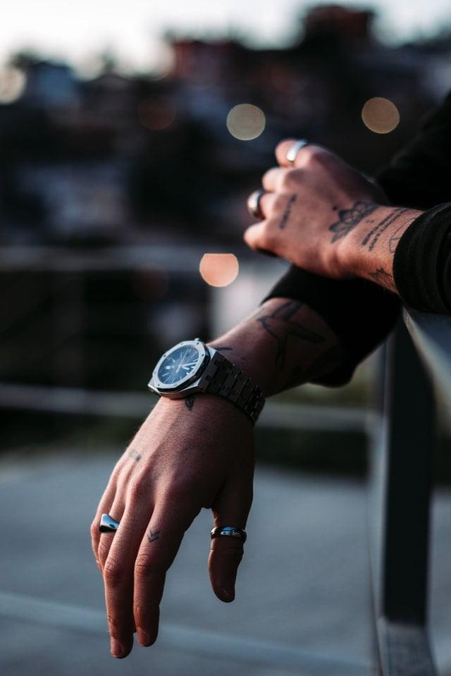 Mão masculina com tatuagem pequena no dedo