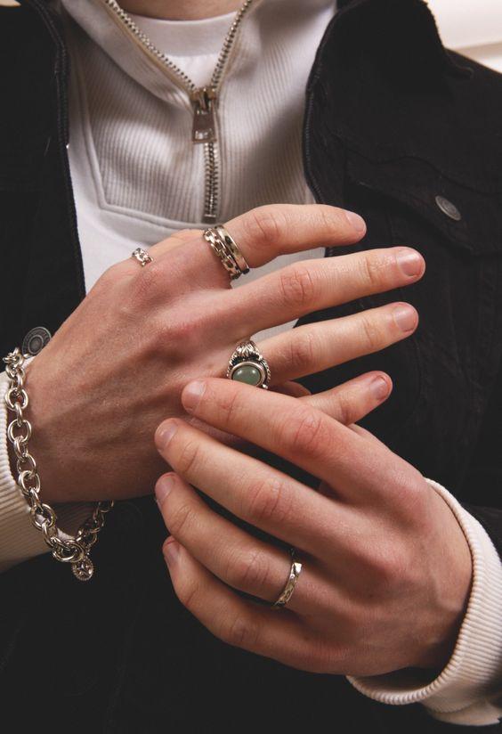 Mão masculina com unhas feitas mexendono anel