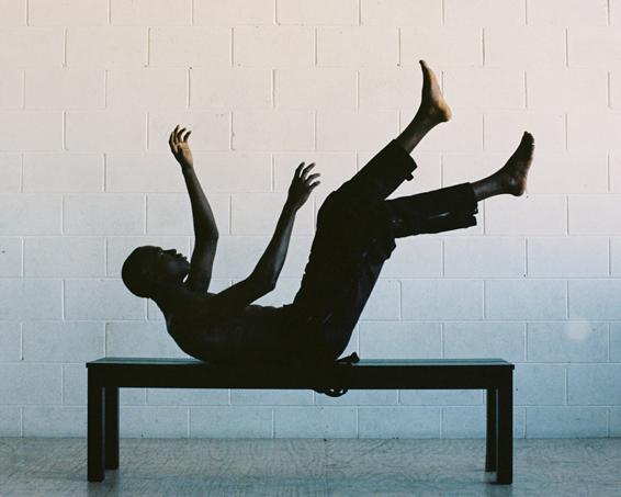 Homem simulando uma queda de costas sobre um banco