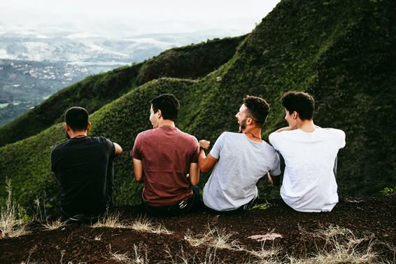 Foto de 4 homens sorrindo, de costas, sentados em uma montanha.
