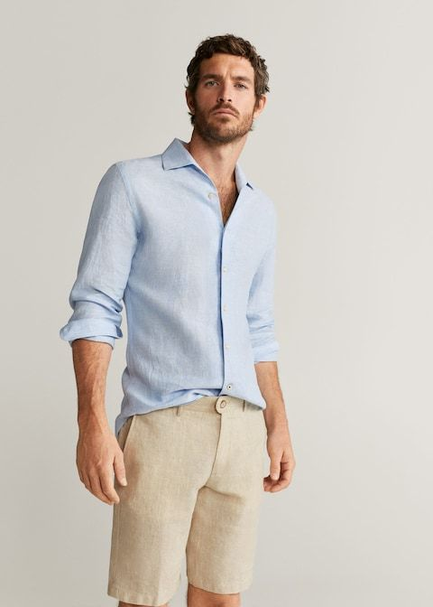 Homem branco com camisa social azul clara e bermuda chino creme