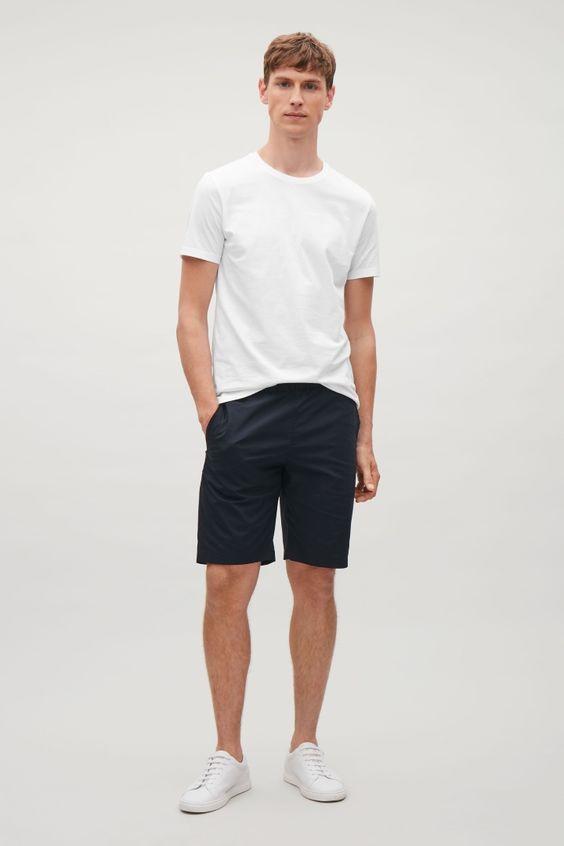 Rapaz branco com camisa branca e bermuda chino preta lisa