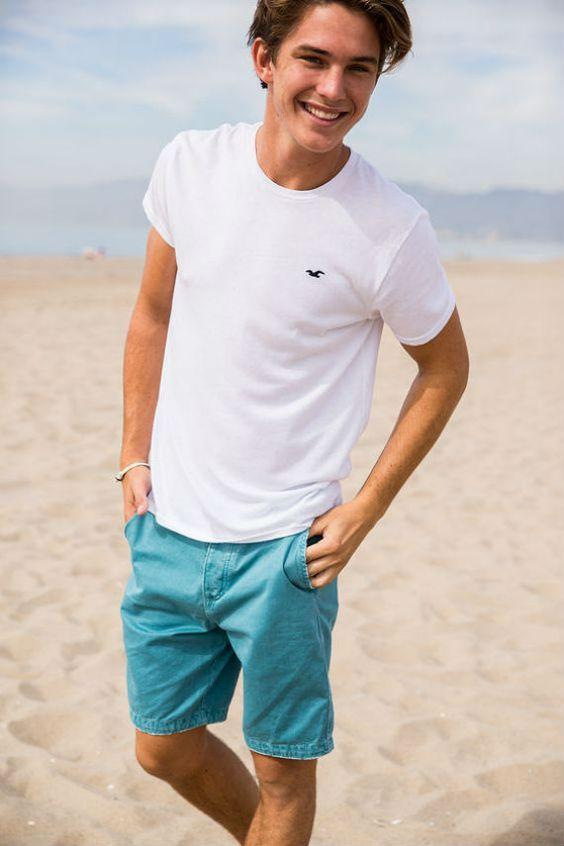 Rapaz branco com camisa branca e bermuda jeans colorida