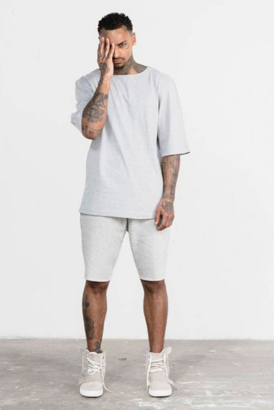 Homem negro usando camisa cinza grande e  bermuda moletom branca