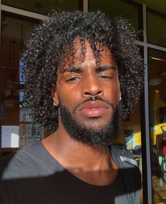 Close em  rosto de rapaz negro com corte médio com camadas