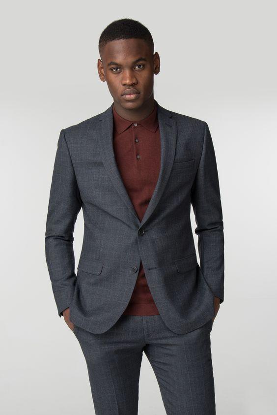 Homem negro de camisa  polo vinho e blazer cinza.