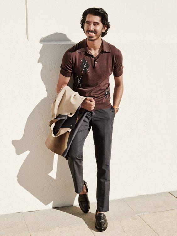 Dev Patel sorrindo com camisa polo masculina marrom e calça social