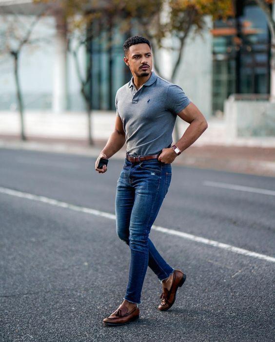 Homem negro com camisa polo masculina cinza e calça jeans clássica.