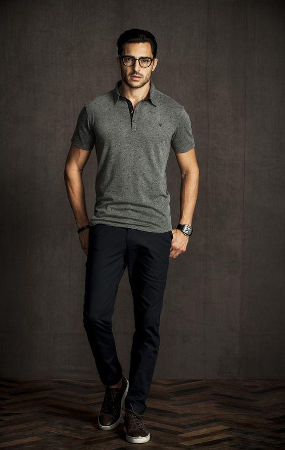 Homem branco  de óculos com camisa polo cinza com estampa minimalista e calça jeans preta