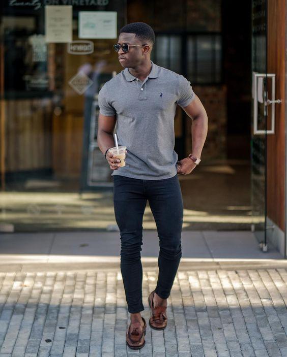 Rapaz negro com camisa polo cinza e  calça jeans escura.