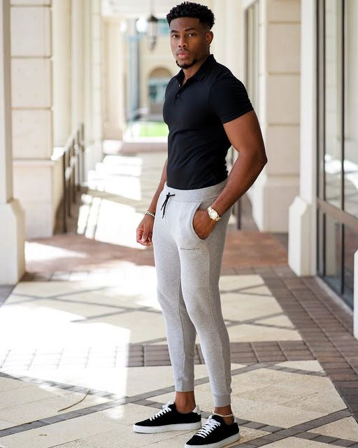 Homem negro com camisa polo masculina preta e calça moletom jogger cinza claro.