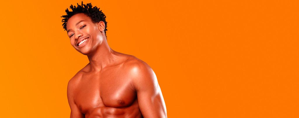 Homem negro sorrindo após passar por uma depilação a laser masculina