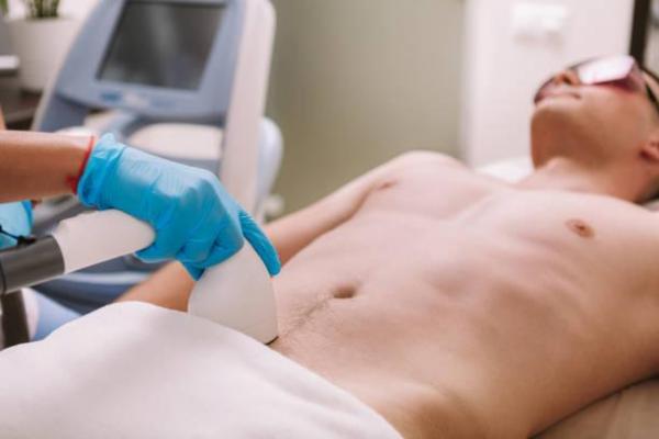 Close no quadril de um homem branco passando por uma sessão de depilação a laser masculina