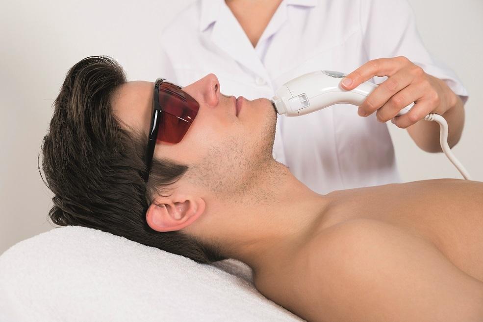 Close no rosto de um homem passando por uma depilação a laser masculina
