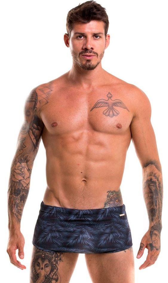 Rapaz branco tatuado com sunga preta tradicional com estampa
